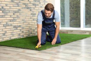man installing indoor artificial grass on the floor